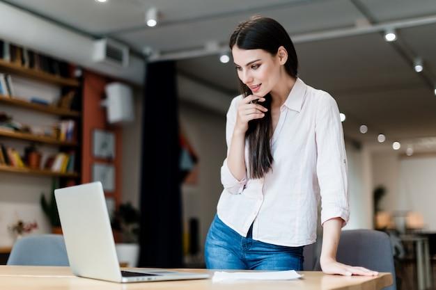 若い女性はラップトップでオフィスで働いています