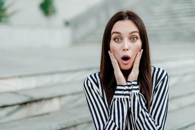 Удивленная и шокированная женщина на улице