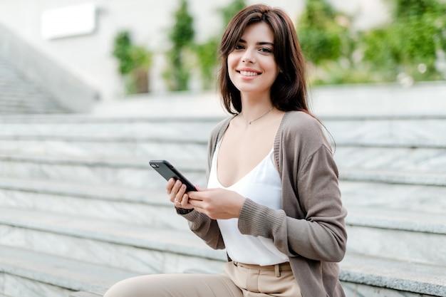 携帯電話で笑顔の女性