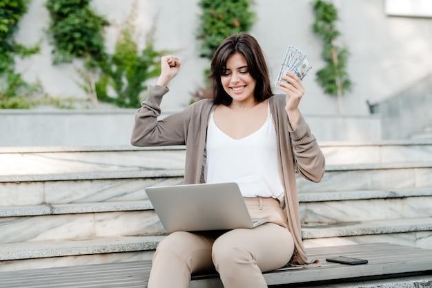幸せな女は屋外のラップトップでお金を稼ぐ