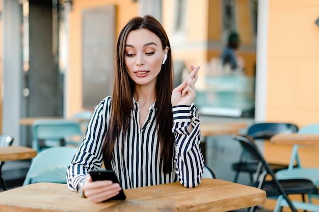 女性は電話を見て、運を期待して交差指を保持しています。