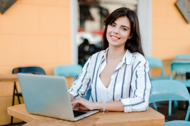 カフェに座っているラップトップで笑顔の女性