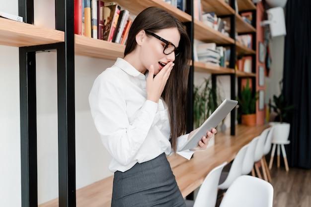 オフィスでタブレットのニュースでショックを受けた女性