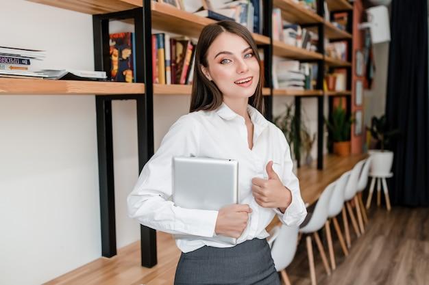 タブレットを持つ女性は、オフィスで親指を表示します