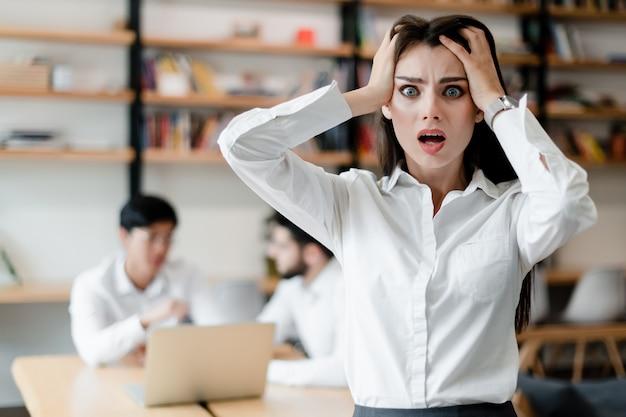 Шокированная женщина в офисе