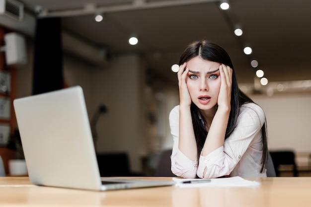オフィスでラップトップで疲れて疲れて混乱している女性