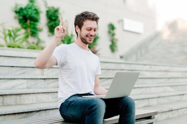 ノートパソコンのウェブカメラに平和のジェスチャーを示す男