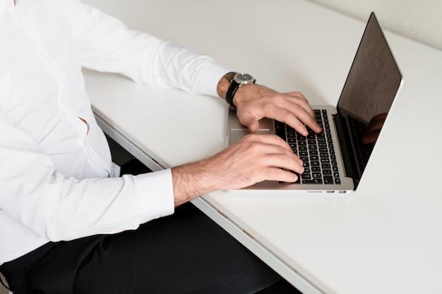 職場でラップトップ上のキーボードで入力する男