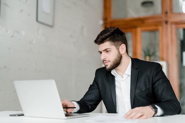 スーツのハンサムな実業家はオフィスでラップトップを使用してください