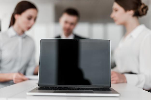 Компьтер-книжка с пустым экраном перед группой сотрудников