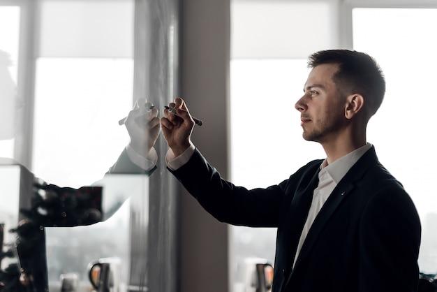 Бизнесмен в офисе рисования диаграмм на стеклянной стене