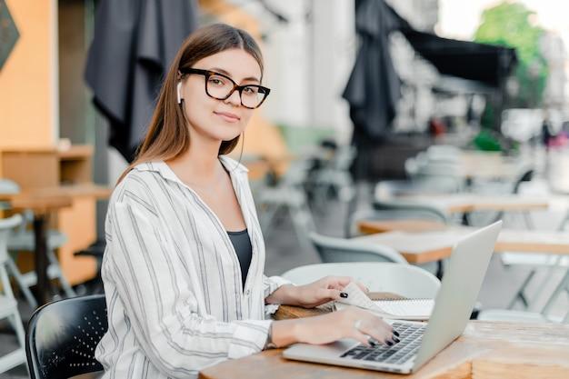 カフェに座ってノートパソコンとメガネの女性の笑みを浮かべてください。