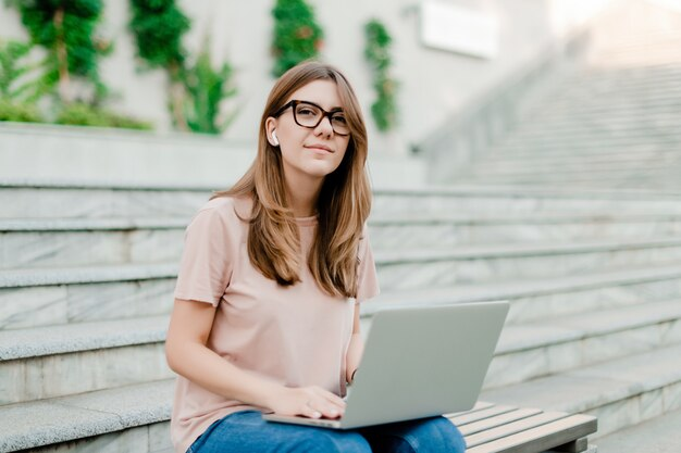 笑みを浮かべて、屋外でリモートで作業のラップトップを持つ若い女性