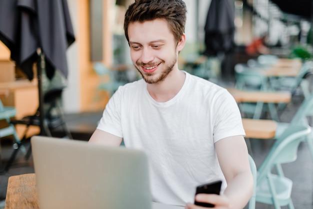 屋外カフェで携帯電話とラップトップでフリーランスの仕事をしている若い男
