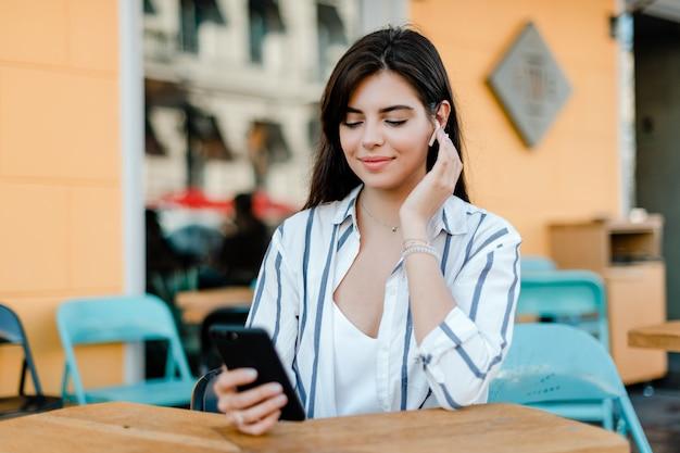 Женщина разговаривает по телефону через беспроводные наушники
