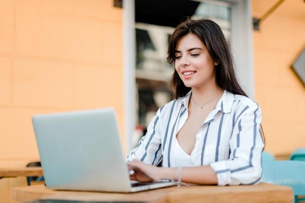 屋外カフェでラップトップ上のフリーランスの仕事をしている女性の笑みを浮かべてください。