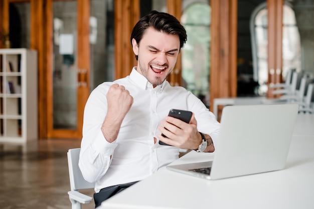 Счастливый человек взволнован победой по телефону в офисе