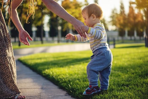 ママは晴れた秋の日に自然の中で緑の芝生の上を歩くかわいい赤ちゃんを助ける