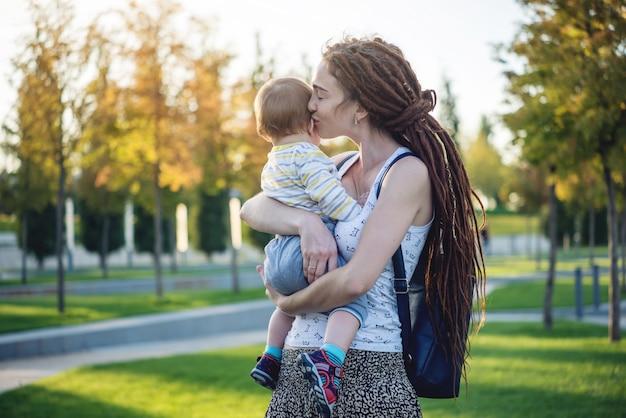 日当たりの良い公園を歩いて赤ちゃんの息子と若い現代幸せなお母さん