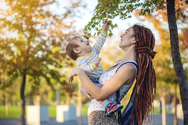 日当たりの良い公園を歩いて赤ちゃんの息子と現代の幸せママ