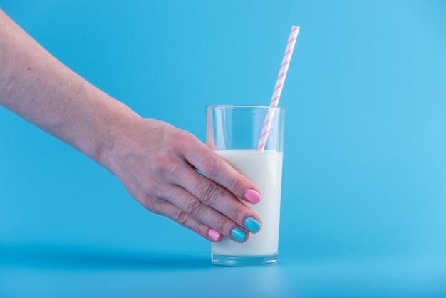 女性の手は、青色の背景にストローで新鮮な牛乳のガラスを保持しています。カルシウムと健康的な乳製品の概念