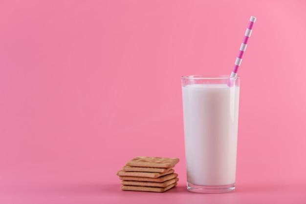 ストローとピンクの背景のクッキーと新鮮な牛乳のガラス。カラフルなミニマリズム。健康的な乳製品