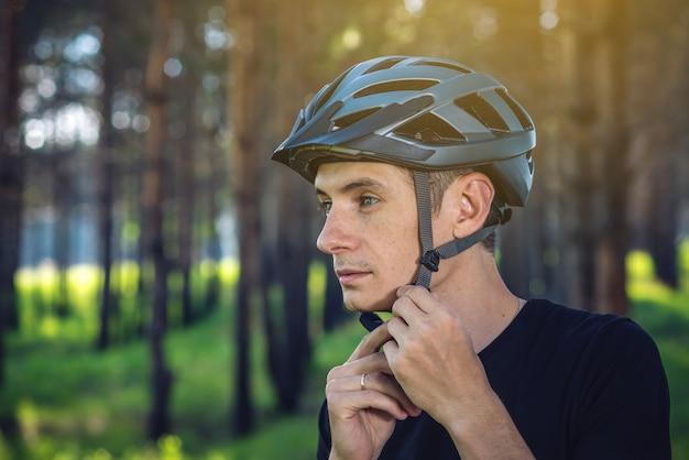 男のサイクリストは、緑の自然の背景に彼の頭に灰色のスポーツヘルメットを着ています。