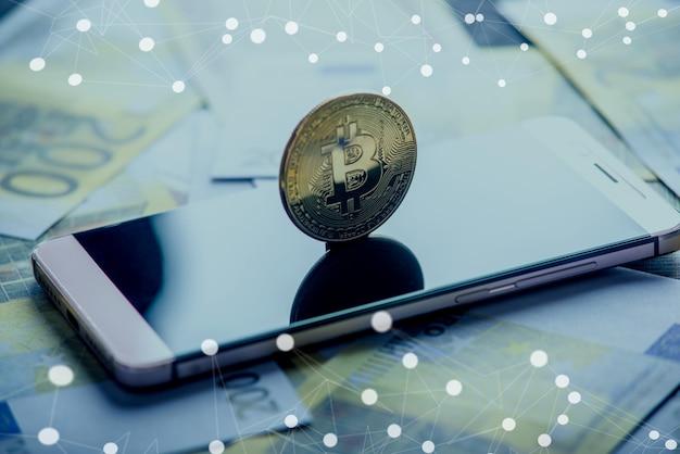Биткойн монеты на экране телефона на фоне банкнот евро. блокчейн и будущее криптовалюты