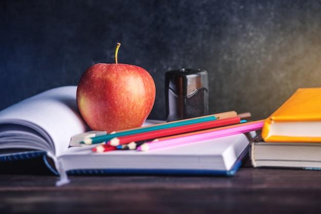 テーブルの上の学用品。本、鉛筆、リンゴは学生のコレクションです。