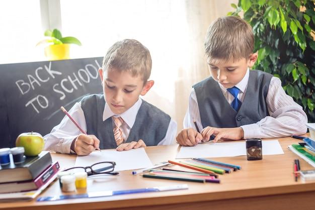 学校に戻る。教室の机に座っているかわいい子供たち。