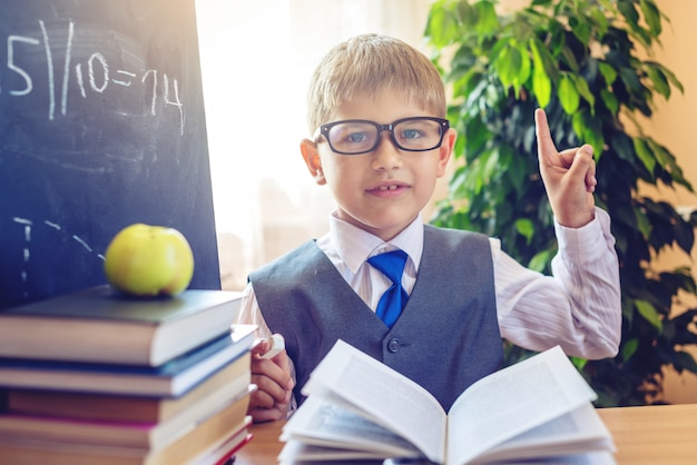 教室の机に座っているかわいい子。少年はレッスン中に重要な情報を発見する