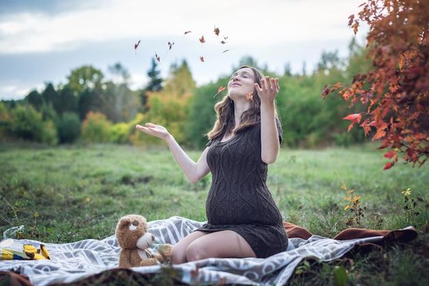 Беременная женщина с животиком сидит на одеяле и подбрасывает желтые листья