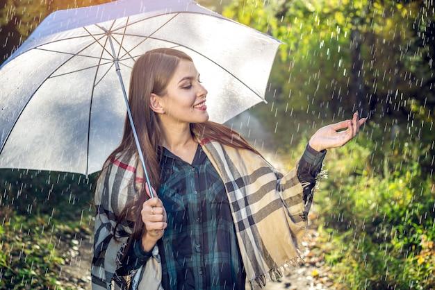 雨の中で白い傘で日当たりの良い公園を歩いて幸せな若い女