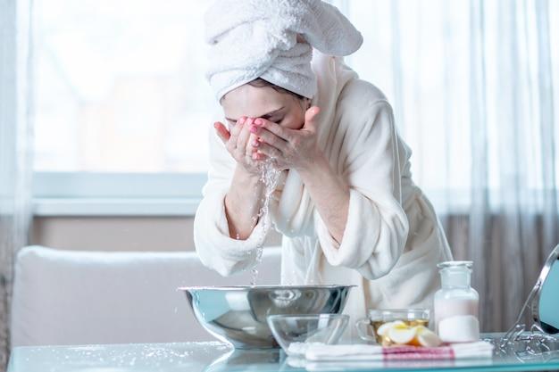 午前中に水で顔を洗う頭にタオルを持つ若い女性。衛生と肌のケアの概念