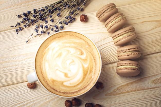 Кофе со взбитыми сливками с макаронами и орехами. идеальный завтрак