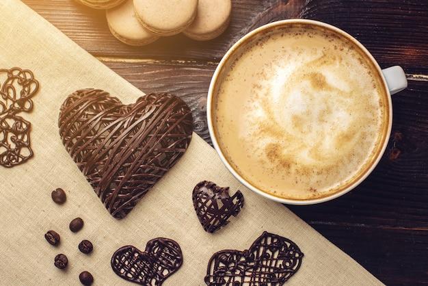 Кофе капучино с красивой пеной, рядом макаруны и шоколадное сердце.