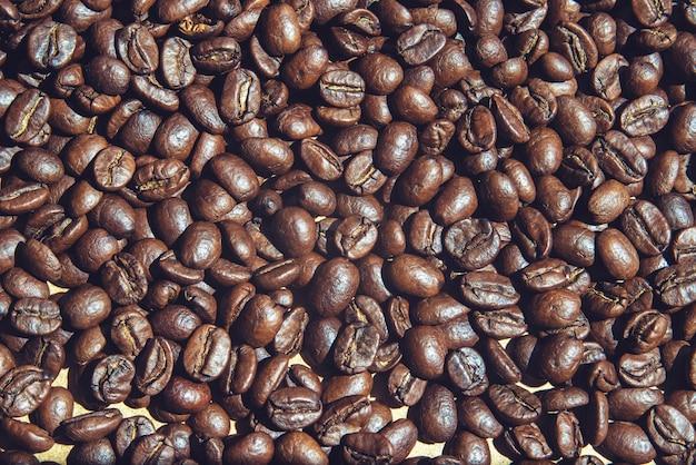 Жареные кофейные зерна на поверхности крупным планом вид сверху, фон