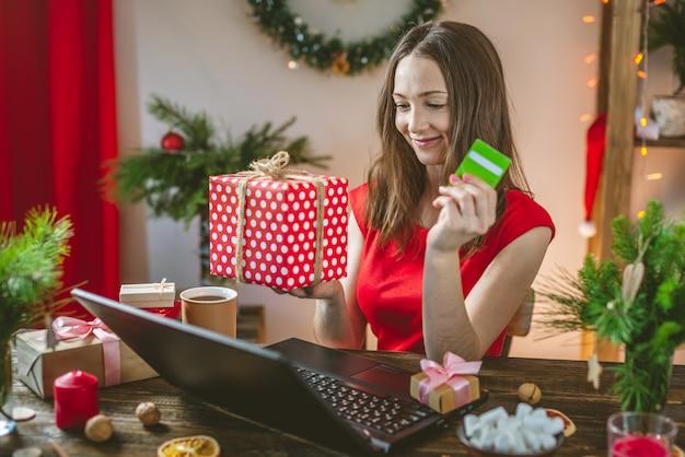 美しい女性はギフト用の箱を保持し、ラップトップでオンライン購入を注文しています。クリスマス休暇のためのオンラインショッピング。