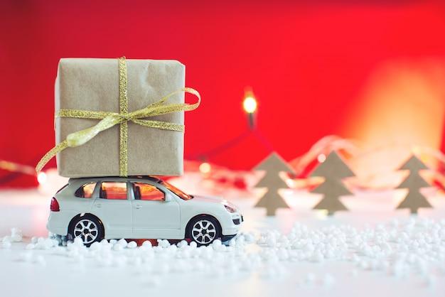 Игрушечный автомобиль несет на крыше подарок на рождество