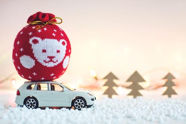 おもちゃの車はクリスマスの屋根の贈り物を運ぶ