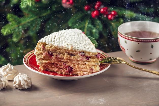Кусок клюквенного пирога, покрытый белым кремом, на тарелке на фоне елки