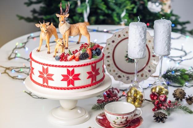 Белый рождественский торт с красным орнаментом сверху украшен мастичными фигурками оленей и свежими ягодами на праздничном столе