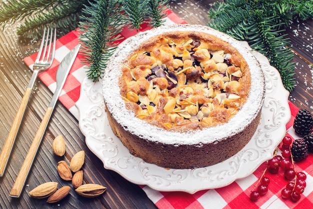 Домашний рождественский или новогодний праздник ягодный пирог с орехами на фоне деревянный стол. праздничные десерты