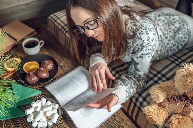 暖かいクリスマスの雰囲気の中で夕方にコーヒーカップと本を読んでセーターの女の子。お正月気分