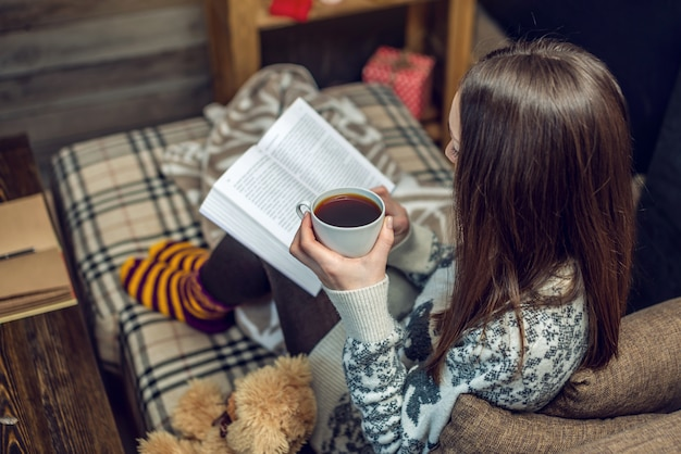 Женщина в свитере читает книгу с кружкой кофе вечером в теплой рождественской атмосфере. уютный новый год настроение