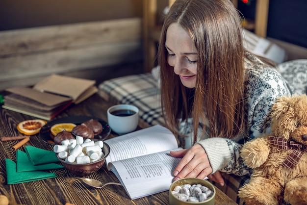 Молодая девушка в свитер, читая книгу с чашкой кофе вечером в теплой атмосфере рождества. новогоднее настроение