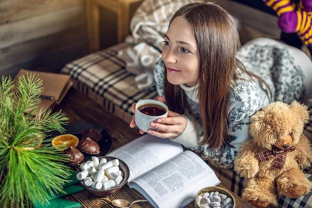 Молодая девушка в свитер, читая книгу с кружкой чая вечером в теплой рождественской атмосфере. новогоднее настроение