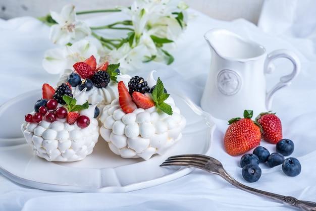 白い表面のプレートに新鮮な果実と繊細な白いメレンゲ。デザートパブロワ。ウエディングケーキ。