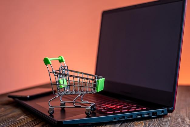 クレジットカード付きのショッピングカートは、画面の前のラップトップの上に立っています。現代生活におけるインターネット上のオンライン購入