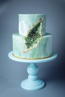 Свадебный торт украшен каменным мрамором с изумрудами в разрезе